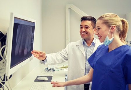 stomatological: people, medicine, stomatology, technology and health care concept - happy dentists looking to x-ray scan on monitor at dental clinic Stock Photo