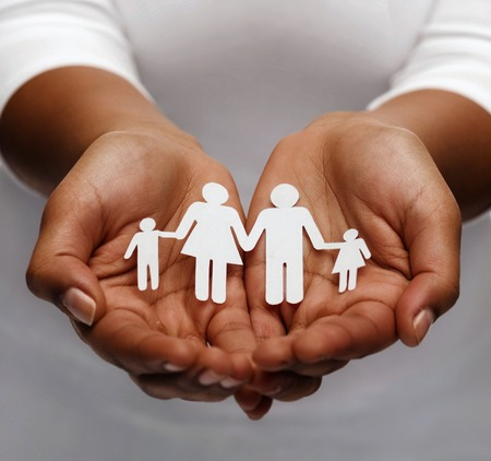 life insurance, love and charity concept - closeup of womans cupped hands showing paper man family