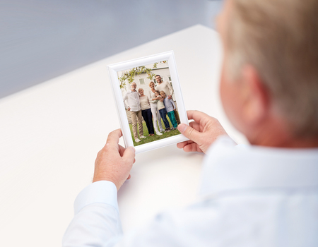 nostalgia: oldness, memories, nostalgia and people concept - close up of old man holding and looking at happy family photo Stock Photo