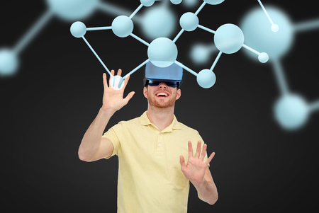 game over: 3d technology, virtual reality, science, biology and people concept - happy young man with virtual reality headset or 3d glasses playing game over black background and molecules Stock Photo