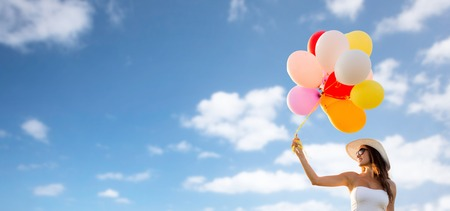 carefree: happiness, summer, holidays and people concept - smiling young woman wearing sunglasses with balloons over blue sky background