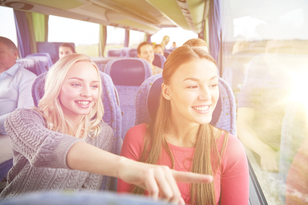 shuttle: transport, tourism, friendship, road trip and people concept - young women or teenage friends riding in travel bus