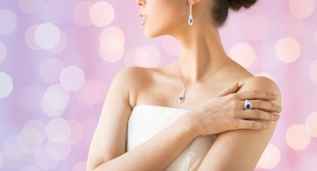 glamour luxury: glamour, beauty, jewelry and luxury concept - close up of beautiful woman with finger ring over pink holidays lights background