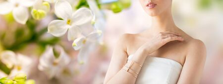 bride bangle: glamour, beauty, jewelry and luxury concept - close up of beautiful woman with golden ring and bracelet over natural spring lilac blossom background