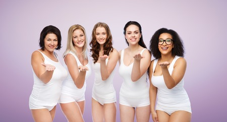 love blow: love, friendship, beauty, body positive and people concept - group of happy plus size women in white underwear sending blow kiss over violet background