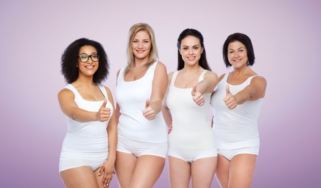 gesture, friendship, beauty, body positive and people concept - group of happy different women in white underwear showing thumbs up over violet background Stock Photo