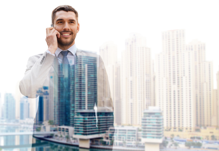 phone business: business, technology, communication and people concept - young smiling businessman calling on smartphone over dubai city background with double exposure effect