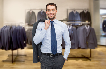 menswear: business, people, menswear, sale and clothes concept - happy young businessman over clothing store background