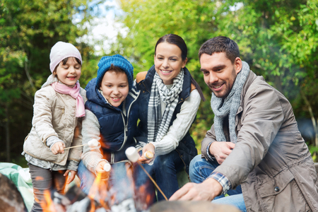 camping, travel, tourism, hike and people concept - happy family roasting marshmallow over campfire Banque d'images