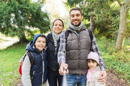 hiking stick: technology, travel, tourism, hike and people concept - happy family with backpacks taking picture by selfie stick and hiking