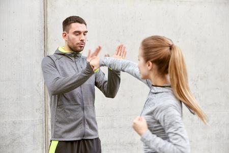 防衛: fitness, sport, people, exercising and martial arts concept - young woman with trainer working out self defense strike on city street 写真素材