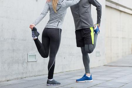 concepto de fitness, deporte, entrenamiento y estilo de vida - cerca de pareja estirando las piernas al aire libre Foto de archivo