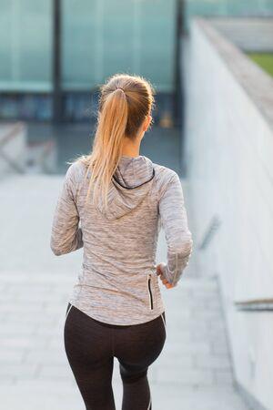 personas corriendo: fitness, deporte, la gente y el concepto de estilo de vida - cerca de la mujer deportiva que se ejecuta abajo en la ciudad