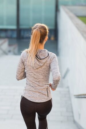 rear view: fitness, sport, people and lifestyle concept - close up of sporty woman running downstairs in city