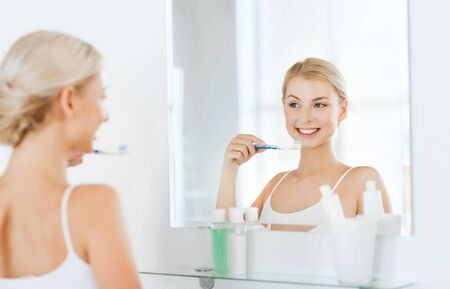 home health care: health care, dental hygiene, people and beauty concept - smiling young woman with toothbrush cleaning teeth and looking to mirror at home bathroom