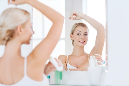 perspiration: beauty, hygiene, morning and people concept - smiling young woman applying antiperspirant or stick deodorant and looking to mirror at home bathroom