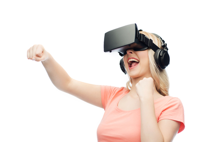 3d technology, virtual reality, entertainment and people concept - happy young woman with virtual reality headset or 3d glasses playing game and fighting Stock Photo