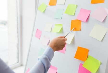 bureau, affaires, les gens et le concept de l'éducation - gros plan de la main avec un stylo pointant vers autocollant blanc sur le tableau blanc