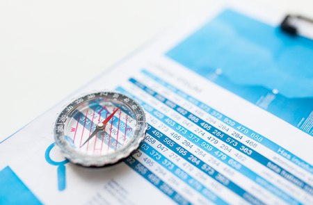 finance report: business, statistics, economy, finance and research concept - close up of compass on financial report document