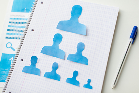 Stil: business, people, employment, career and hiring concept - close up of paper human shapes on notebook Stock Photo