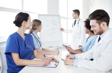 medical drawing: medical education, health care, medical education, people and medicine concept - group of happy doctors or interns with mentor meeting and drawing on flip board on presentation at hospital Stock Photo