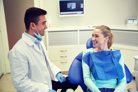 patient care: people, medicine, stomatology and health care concept - happy male dentist with woman patient talking at dental clinic office