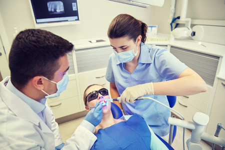 treating: people, medicine, stomatology and health care concept - male dentist and assistant with dental curing light and mirror treating female patient teeth at dental clinic office