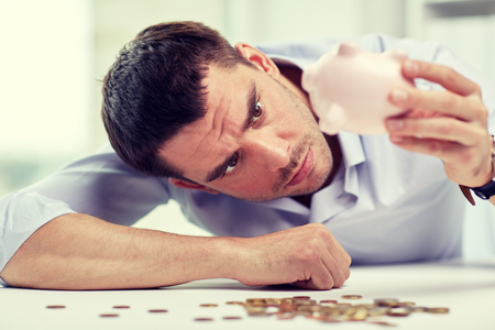 few: business, people, finances, crisis and money saving concept - businessman shaking piggy bank and getting coins at office Stock Photo
