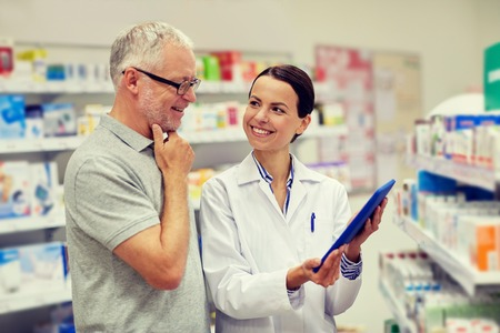 pharmaceutics: medicine, pharmaceutics, health care and people concept - happy pharmacist with tablet pc computer and senior man customer at drugstore