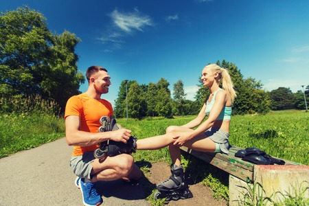 rollerblades: fitness, sport, summer, couple and healthy lifestyle concept - happy man helping woman to put on rollerblades outdoors Stock Photo