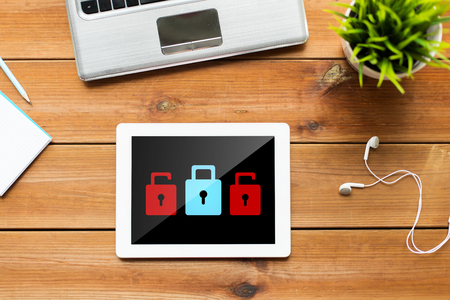 web security: business, cyber protection, web security and technology concept - close up of tablet pc computer, laptop and earphones on wooden table with padlock icons on screen