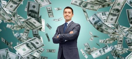 business, finance, investeringen, economie en mensen concept - gelukkig zakenman over dollar contant geld regen en groene achtergrond Stockfoto