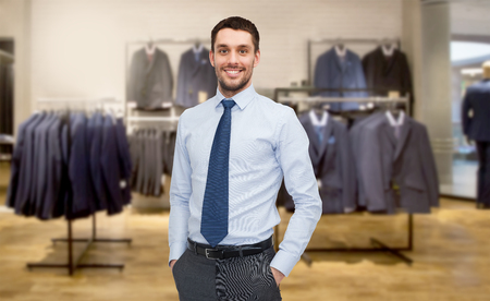 formal dressing: business, people, menswear, sale and clothes concept - happy young businessman over clothing store background