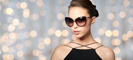 eyewear fashion: accessories, eyewear, fashion, people and luxury concept - beautiful young woman in elegant black sunglasses over holidays lights background