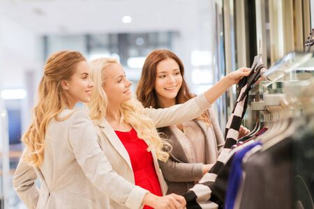 choosing clothes: sale, consumerism and people concept - happy young women choosing clothes in mall