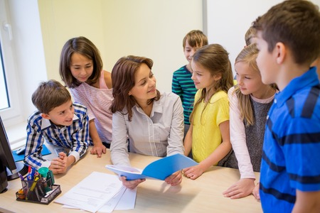 elementary: education, elementary school, learning and people concept - group of school kids with teacher talking in classroom