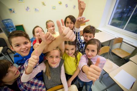 Educación, escuela primaria, el aprendizaje, el gesto y el concepto de personas - grupo de niños de la escuela y que muestra los pulgares para arriba en el aula Foto de archivo - 62353464