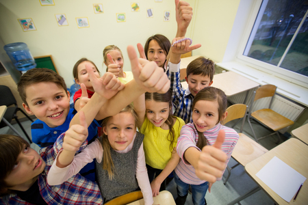 thumbs up group: education, elementary school, learning, gesture and people concept - group of school kids and showing thumbs up in classroom