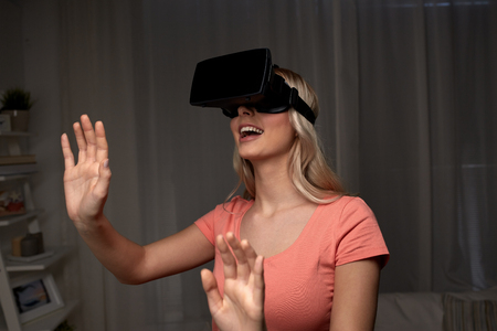 mediated: technology, virtual reality, entertainment and people concept - happy young woman with virtual reality headset or 3d glasses playing game at home and touching something invisible