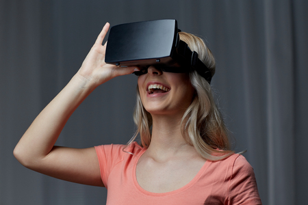 entertainment concept: technology, virtual reality, cyberspace, entertainment and people concept - happy young woman with virtual reality headset or 3d glasses at home Stock Photo
