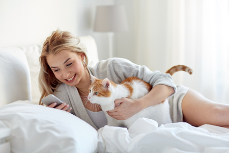 technology, pets, communication and people concept - happy young woman with cat and smartphone texting message in bed at home