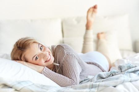 休息、睡眠、快適さと人々 のコンセプト - 寝室自宅のベッドで横になっている幸せな若い女