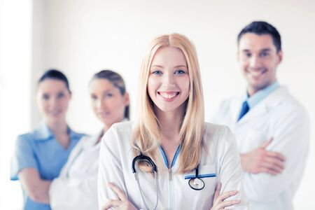 physicians: attractive female doctor in front of medical group Stock Photo