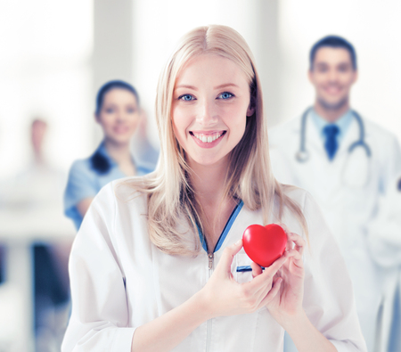 medics: healthcare and medical concept - female doctor with heart