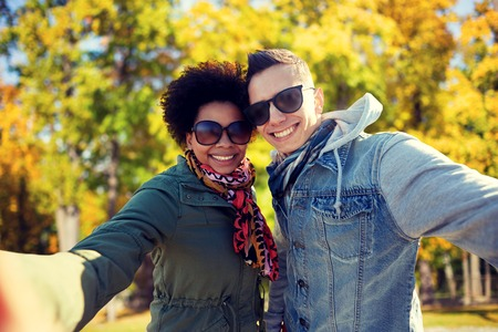 multiracial: tourism, travel, people, season and technology concept - happy teenage international couple taking selfie over autumn park background