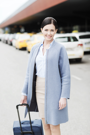 trip over: travel, business trip, people and tourism concept - smiling young woman with travel bag over taxi at airport terminal or railway station