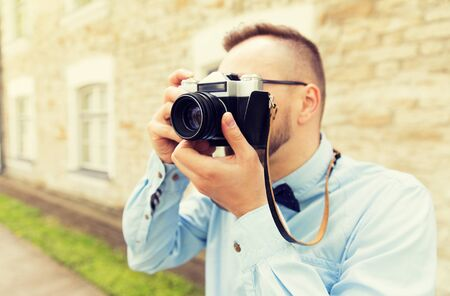 one man: people, photography, technology, leisure and lifestyle - close up of young hipster man with retro vintage film camera on city street Stock Photo