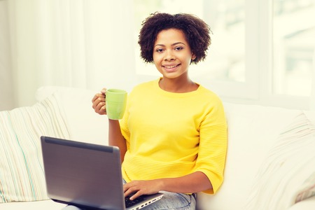 happy african: people, technology and leisure concept - happy african american young woman sitting on sofa with laptop computer and drinking tea from cup at home Stock Photo