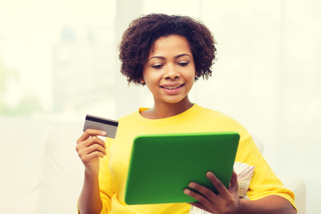 shopping card: people, internet bank, online shopping, technology and e-money concept - happy african american young woman sitting on sofa with tablet pc computer and credit card at home