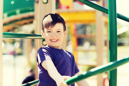 climbing frame: summer, childhood, leisure and people concept - happy little boy on children playground climbing frame Stock Photo
